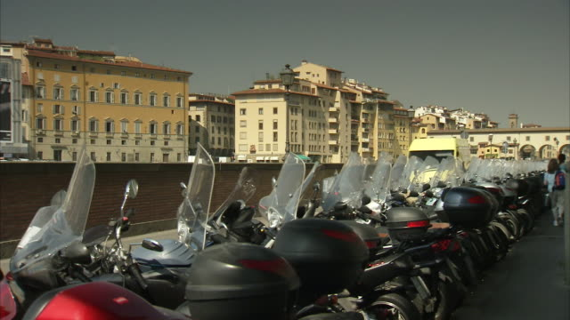 Parked mopeds line a city street in Florence, Italy.