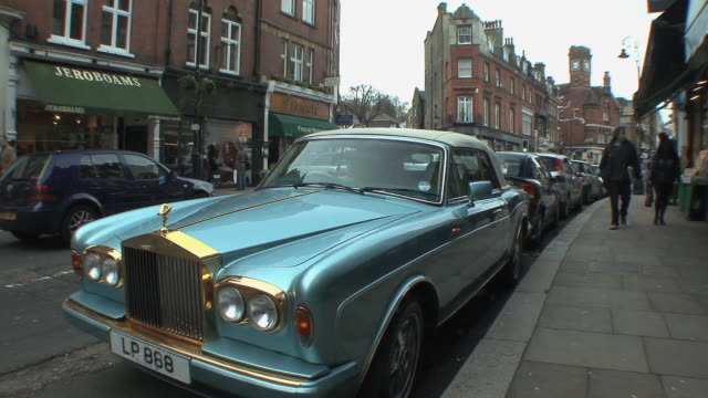 ws pan parked rolls royce and fancy shops on high street in hampstead / london, uk.  - rolls royce stock videos and b-roll footage