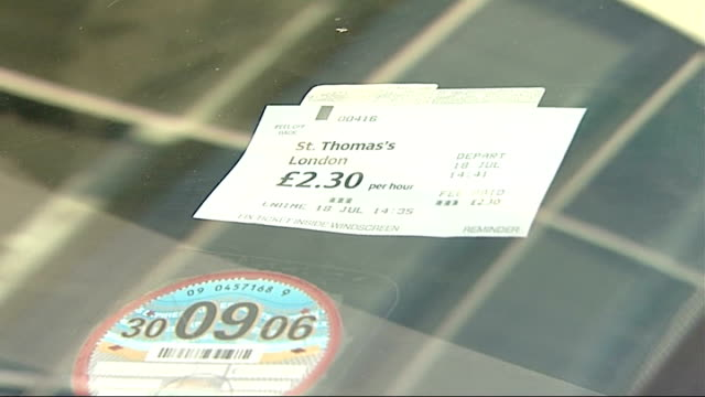parking and telephone costs for patients and relatives arm of man as he places 'pay and display' ticket in windscreen of car zoom in close up of... - parking ticket stock videos & royalty-free footage
