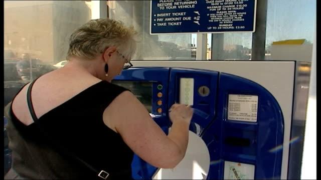 vídeos de stock e filmes b-roll de parking and telephone costs for patients and relatives; england: london: hampstead: ext valerie penfare placing coins into slot of parking ticket... - estacionar