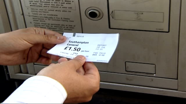 vídeos de stock e filmes b-roll de parking and telephone costs for patients and relatives; ext hand removing parking ticket from machine in hospital carpark side view of patient... - estacionar