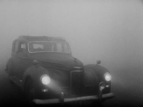 a parking attendant guides a car through thick fog at alexandra palace - 1952 stock videos and b-roll footage
