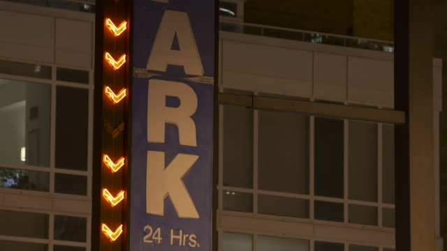 parking garage sign with blinking neon arrows. - blinking arrow stock videos & royalty-free footage