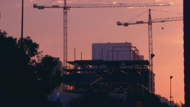 vídeos de stock, filmes e b-roll de parking lot and city construction - inclinação para cima
