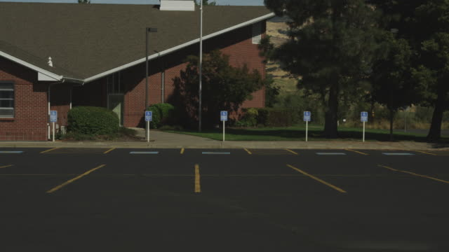 a parking lot fronts a brick church with a steeple. - steeple stock videos & royalty-free footage