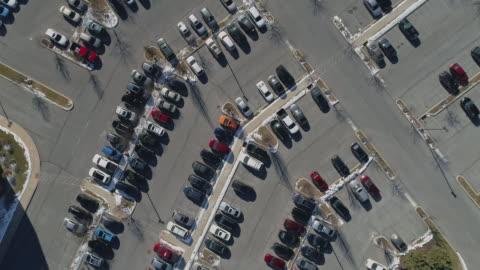商業和購物中心附近的停車場由汽車完成。平移攝像機運動。 - parking 個影片檔及 b 捲影像