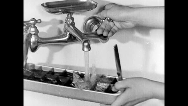 vidéos et rushes de parkinson daughter fill ice trays from the kitchen tap and puts in electric freezer / hazel parkinson puts the oil lamp away in cupboard / young son... - electric lamp