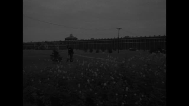parklike inner courtyard of prison / with walls of facility in distance an inmate rakes in flowering field / entrance to michigan state prison /... - michigan stock videos and b-roll footage