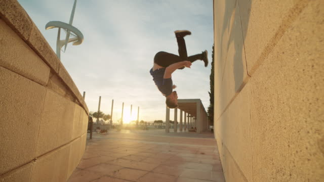 vídeos de stock, filmes e b-roll de parkour man backflipping between walls and touching both - agilidade