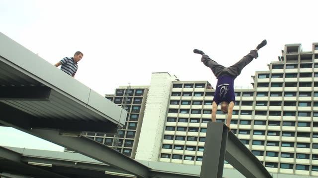 parkour, men jump over railing, one man do a handstand