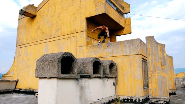 parkour on the roof of the building - tracksuit bottoms stock videos & royalty-free footage