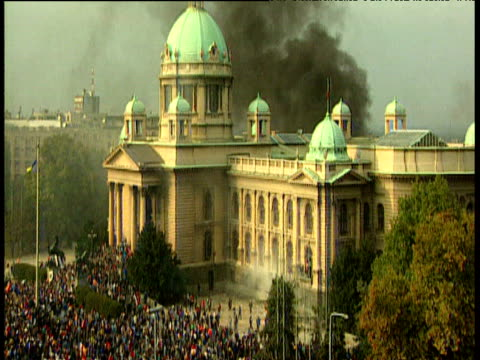 vídeos de stock, filmes e b-roll de parliament building on fire with thousands of serbian protestors surrounding the building belgrade; 05 oct 00 - sérvia