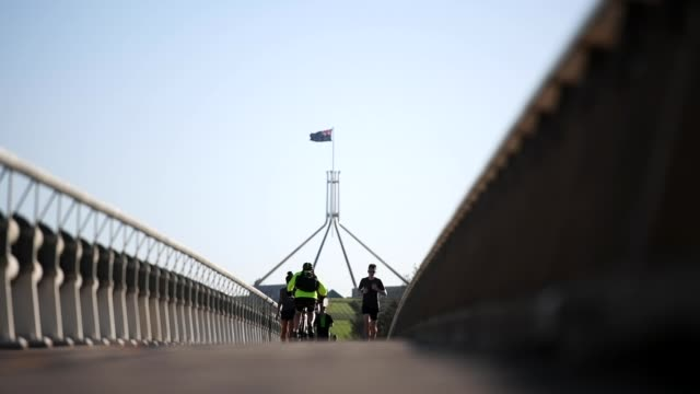 parliament house is seen behind as people exercise near lake burleygriffin on march 20 2020 in canberra australia the australian government has... - parlamentsgebäude regierungsgebäude stock-videos und b-roll-filmmaterial