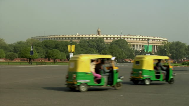 ws, parliament house, traffic on street in foreground, new delhi, india - fahrradtaxi stock-videos und b-roll-filmmaterial