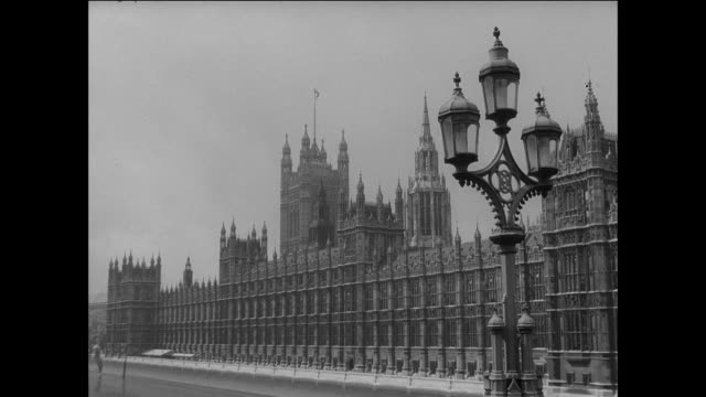 vidéos et rushes de parliament legislates at palace of westminster / london uk / buses drive over river thames bridge / flag waves over palace of westminster / motor... - parlement britannique