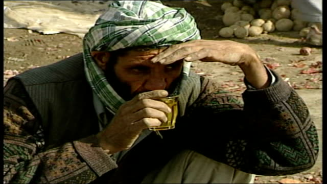 vidéos et rushes de women's role; ext general view of women and men along in busy street afghan man crouching drinking from a glass general view of busy market afghan... - kaboul