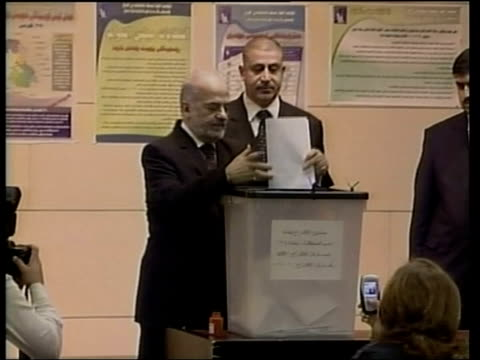 High turnout across the country Baghdad INT Ibrahim alJaafari putting his finger in ink and dropping his voting paper into box WIPE TO Ayad Allawi...