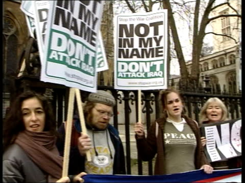 vídeos de stock, filmes e b-roll de parliamentary vote on un resolution itn england london peace protestors standing behind banner with 'don't attack iraq' and 'not in my name' placards... - stop placa em inglês
