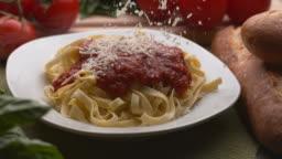 Parmesan cheese sprinkled onto pasta