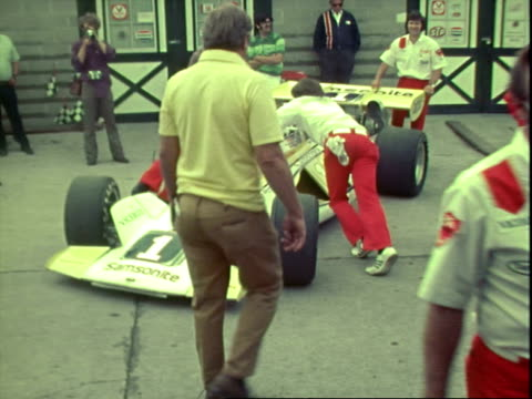 parnelli jones team formula one race car being pushed from shed by pit crew prerace indianapolis 500 / pit crew pushing jones team f1 car from shed... - anno 1972 video stock e b–roll