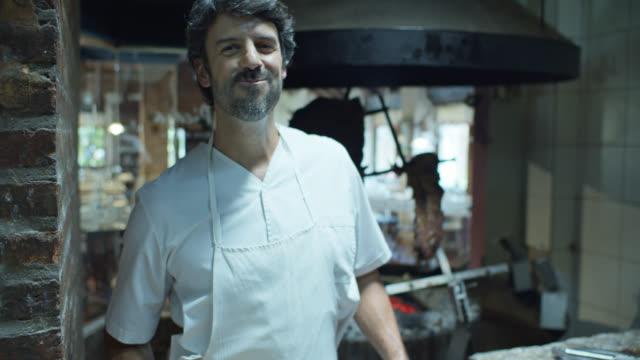 vídeos de stock, filmes e b-roll de parrilla chef mastigando comida e sorrindo - argentina