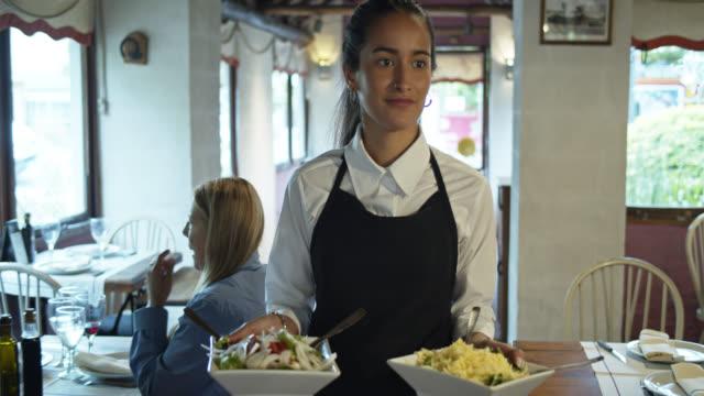 vídeos de stock e filmes b-roll de parrilla waitress bringing side dishes to table - empregada de mesa