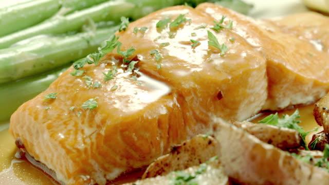 vídeos de stock e filmes b-roll de parsley falls on a salmon steak dish. - filete de salmão