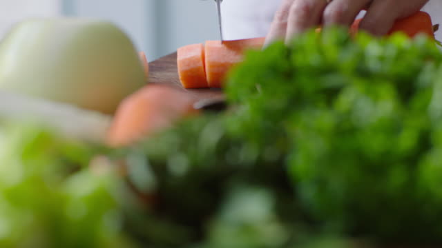 parsley, rosemary and onion sit on a board where a large carrot is being chopped, uk. - vegetable stock videos & royalty-free footage