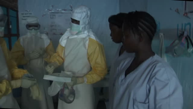 part 1 of 3 interiors showing ebola victim being treated in makeshift hospital, doctors dressed in full contamination suits spray ebola case victim... - victim stock videos & royalty-free footage