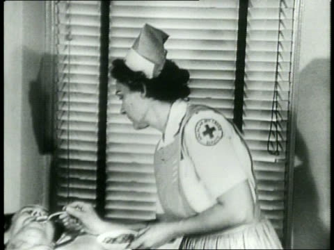 / part 2 / irene dunne / a red cross nurse speaks to a male veteran patient face down on a cot covered with a sheet / a red cross nurse stands over a... - young war veteran stock videos & royalty-free footage