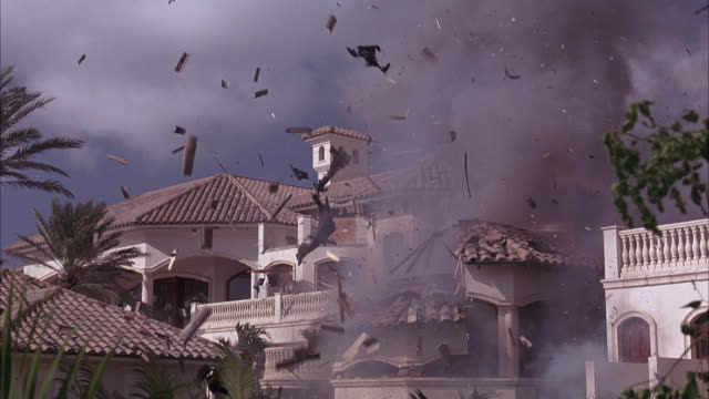 Part of a mansion explodes from the inside.