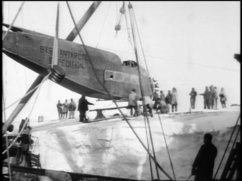 part of airplane for byrd's antarctic expedition hanging from crane / documentary - anno 1928 video stock e b–roll