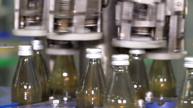 part of automatic machine working all time for filling the herb beverage and tight bottle cap - bottle cap stock videos & royalty-free footage