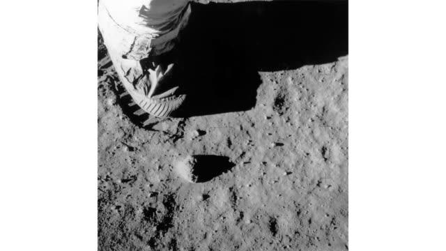 vídeos de stock e filmes b-roll de part of buzz aldrin's leg, foot and footprint on the surface of the moon during the apollo 11 lunar mission. - pegada