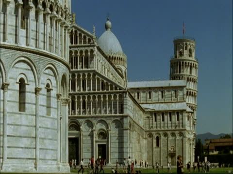 stockvideo's en b-roll-footage met ms part of circular baptistery with top of leaning tower of pisa in background, tuscany - rond de 12e eeuw