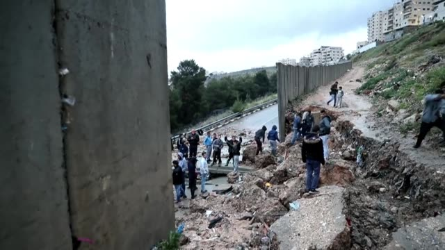 stockvideo's en b-roll-footage met part of israel's controversial separation wall diving the shuafat refugee camp in east jerusalem from the israeli settlement of pisgat zeev collapsed... - oost jeruzalem