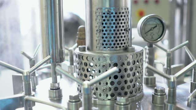 vídeos de stock, filmes e b-roll de peça de uma máquina na fábrica farmacêutica: câmera lenta - medindo