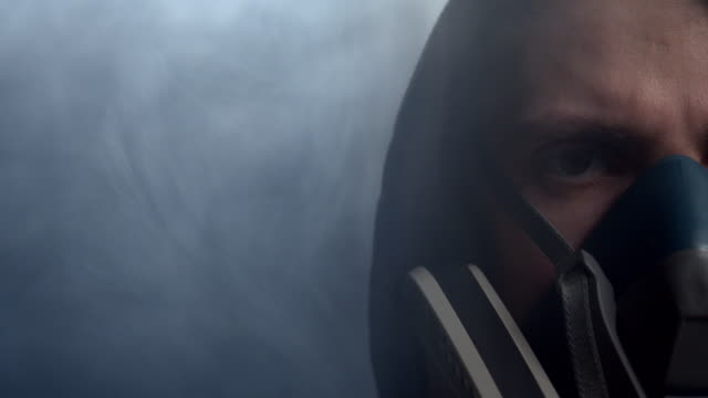 vídeos de stock e filmes b-roll de a part of man's face in the protective mask in the smoke surrounding him. - europe
