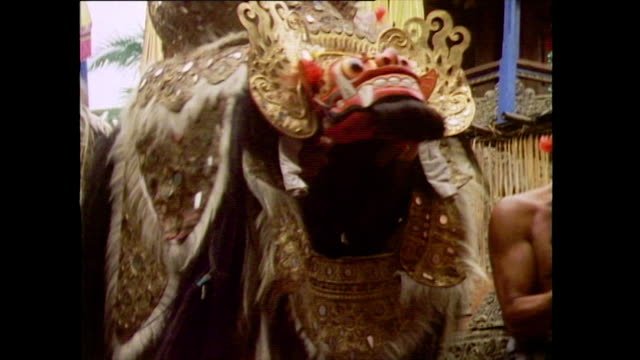 part of the barong dance being performed in bali 1985 closeup of lion's head with moving mouth barong turns and leaves chasing soldiers - pacific islander stock videos & royalty-free footage