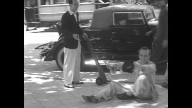 part of william randolph hearst's tour of spain man pushing another on hand truck and woman walking out of maybe a hotel hand truck stops and man... - passing a note stock videos & royalty-free footage