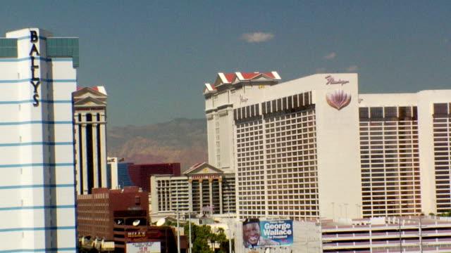 partial bally's hotel & casino building far frame & flamingo hotel casino building frame, clouds passing in clear blue sky bg. las vegas strip, the... - bally's las vegas stock videos & royalty-free footage