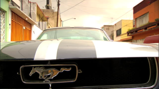 ms partial front of ford shelby mustang w/ silver mustang logo badge on grill parked on unidentifiable street muscle car vintage coupe - ford mustang stock videos and b-roll footage