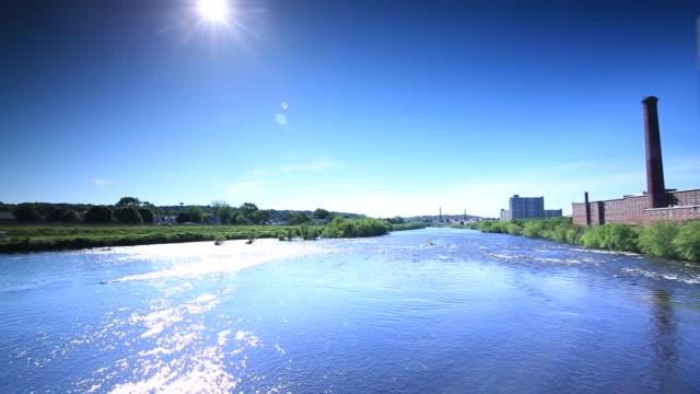 partial historic aiken street bridge spanning merrimack river white hot sun in blue sky brick buildings w/ smokestacks on shoreline - lowell stock videos & royalty-free footage