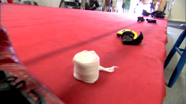 partial jumping rope boxing gloves untied wrapping tape other minor equipment on edge of boxing gym in unidentifiable gym unidentifiable people... - untied stock videos and b-roll footage