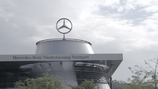 Partial MercedesBenz automobile sales center w/ rotating company symbol on roof gray clouds in sky