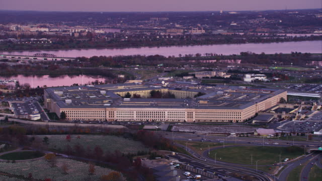 partial orbit of the pentagon from arlington national cemetery with cityscape of washington dc across potomac river in background. shot in 2011. - the pentagon stock videos and b-roll footage