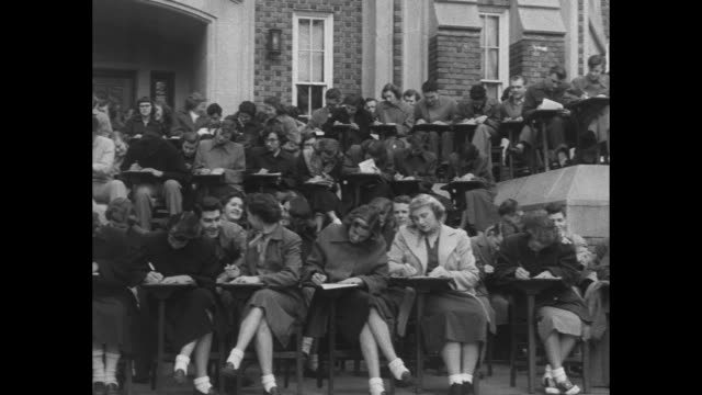 ws partial side view of students on steps in front of building on campus of lenoirrhyne college / ws head on view of students seated with building in... - paramount building stock videos and b-roll footage