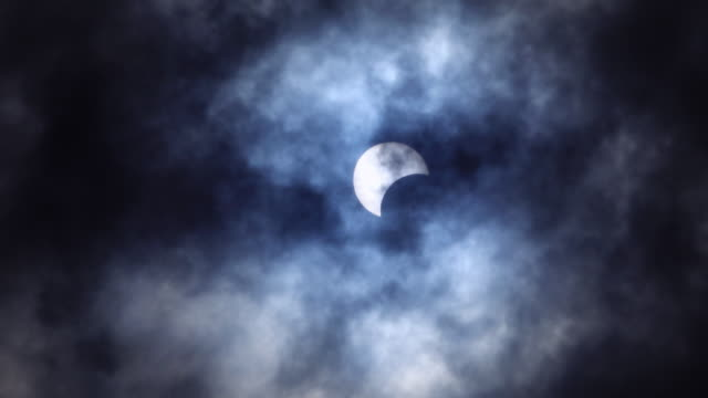 partial solar eclipse in blue dark color with moving cloud - part of stock videos & royalty-free footage