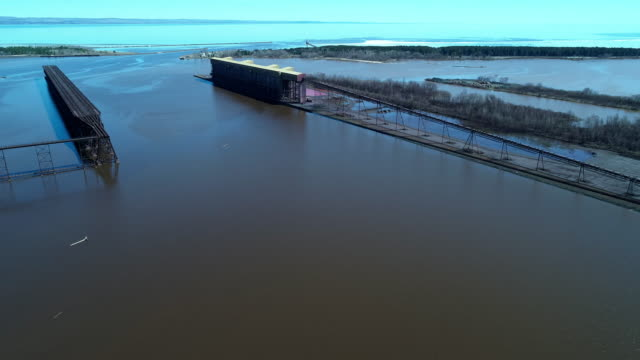 partially abandoned industrial structures in the ships' - railroad loading zone at the lake superior, one of the american great lakes, at the border between minnesota and wisconsin. aerial video footage with the panoramic camera motion. - lago superiore video stock e b–roll