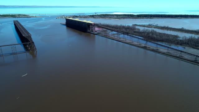 stockvideo's en b-roll-footage met gedeeltelijk verlaten industriële structuren in de schepen '-railroad laadzone aan de lake superior, een van de amerikaanse grote meren, op de grens tussen minnesota en wisconsin. antenne videobeelden met de panoramische camera beweging. - kwaliteit